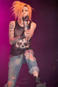 J Fashion Visual Kei lead singer with orange hair, skull shirt and ripped jeans